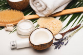 coconut half, cosmetic cream, massage towel, sponges and palm leaves on white surface