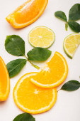 orange and lime slices near rose leaves on white surface