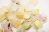 Photo refreshing floral, vegetable and fruit ice cubes for facial care on white