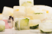 Photo close up view of blurred stack of fruit and vegetable ice cubes on white surface isolated on black