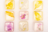 Photo transparent floral and fruit frozen ice cubes on white surface