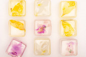 Photo top view of frozen fruit and floral ice cubes on white background