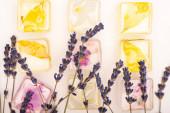 horní pohled na transparentní ovoce a květinové kostky ledu s levandulovými květy na bílém pozadí