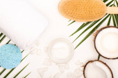top view of coconut halves and flakes, cosmetic cream, towel and massage brush near palm leaves on white