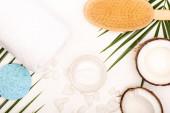 vrchní pohled na kokosové půlky a vločky, kosmetický krém, ručník a masážní kartáč v blízkosti palmových lístků na bílém