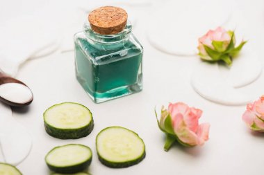 Cucumber slices near corked bottle of homemade lotion, tea roses, and cotton pads on white blurred background stock vector