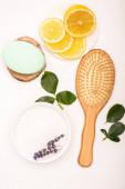 vrchní pohled na štětec, mísu s levandulí, plátky citronu, mýdla a růžové listy na bílém