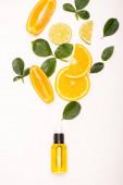 láhev citrusové esence poblíž pomerančových plátků a růžových lístků na bílém povrchu