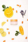 top view of homemade cosmetic cream near sliced orange and lime, almonds, lavender twigs and rose leaves on white