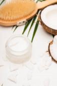 kokosové půlky a vločky v blízkosti domácí kosmetické smetany a masážní štětec na rozmazaném pozadí