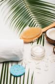 Kokosnusshälfte, kosmetische Creme, Handtuch, Massagebürste und Schwamm in der Nähe von Palmblättern auf weiß