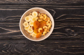 top view of delicious granola with nuts, banana and dried apricots on wooden black surface