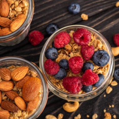 Closeup of delicious granola with berries, dried apricots, nuts and yogurt in glass cups on wooden surface stock vector