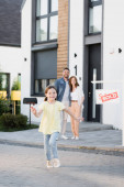 Šťastná dcera běží s rozmazané táta a maminka objímající na pozadí v blízkosti domu