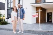 Plná délka šťastného páru při pohledu na kameru a objímání při stání u cedule s prodaným nápisem a domem