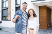 Šťastný muž s klíčem objímání žena při pohledu na kameru s rozmazaný dům na pozadí