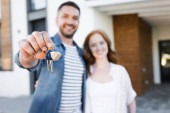 Keys and fob in hand of happy man hugging woman near house on blurred background