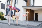 Dcera s šťastnou maminkou a tatínkem drží americkou vlajku jít dopředu v blízkosti znamení s prodaným písmem a dům