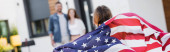 Back view of daughter with american flag near blurred parents on background, banner
