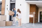 Usmívající se manžel s lepenkovou krabicí při pohledu na manželku držící se za ruce s dcerou v blízkosti domu a podepsat s prodaným nápisem