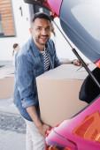 Glücklicher Mann blickt auf Kamera, während er Karton aus dem Kofferraum nimmt