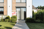 Fotografie Fassade eines modernen Hauses in Rasennähe und Schild mit verkauftem Schriftzug