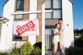 Fotografie Schild mit verkauftem Schriftzug mit verschwommenem Paar, das sich in der Nähe des Hauses umarmt