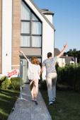 Zadní pohled na pár s rukama ve vzduchu v blízkosti cedule s prodaným nápisem a moderním domem