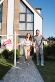 Fotografie Fröhliches Paar Händchen haltend beim Vorwärtslaufen in der Nähe von Schild mit verkauftem Schriftzug und modernem Haus