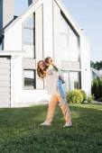 Usmívající se matka piggybacking dcera v blízkosti moderního domu