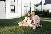 Šťastná rodina při pohledu na kameru, zatímco sedí na trávníku v blízkosti moderního domu