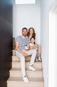 Šťastná rodina s medvídkem a soškou domu při pohledu do kamery, zatímco sedí doma na schodech
