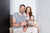 Šťastný muž ukazuje klíče při sezení na schodech v blízkosti ženy se soškou domu a dívka s plyšovým medvídkem doma