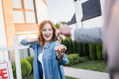 Photo Excited redhead woman with open mouth taking keys from broker with blurred hand on foreground
