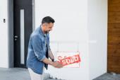 Pozitivní vousatý muž drží ceduli s prodaným nápisem v blízkosti domu