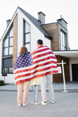 Back view of daughter with mom and dad covered with american flag while standing together near house stock vector