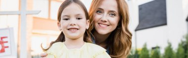 Portrait of happy mother and daughter looking at camera on blurred background, banner stock vector