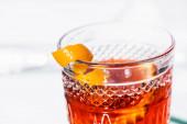 Nahaufnahme von Orangenschalen im Glas mit Alkoholcocktail auf Weiß