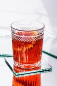 egy szelet narancs kevert alkoholos koktélban fehér alapon