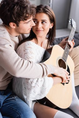 Smiling woman playing acoustic guitar and looking at boyfriend at home stock vector