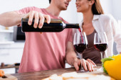 Cropped view of man pouring wine in glass near girlfriend on blurred foreground