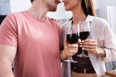 Cropped view of glasses of wine in hands of smiling couple on blurred background in kitchen stock vector