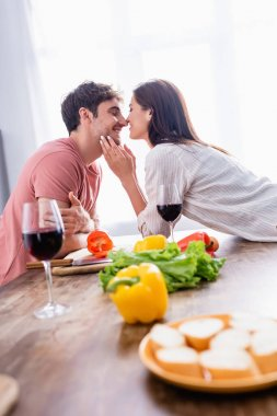 Smiling woman kissing boyfriend near vegetables and glasses of wine on blurred foreground stock vector