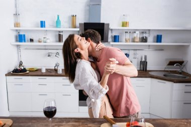 Smiling woman dancing with boyfriend near glasses of wine on blurred foreground in kitchen stock vector