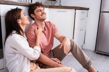 Young woman hugging cheerful boyfriend on kitchen floor stock vector