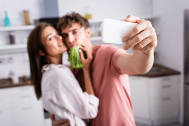 Smartphone in hand of young man taking selfie near girlfriend with lettuce on blurred background stock vector