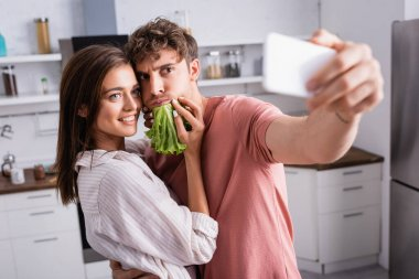 Smiling woman holding lettuce near boyfriend taking selfie on smartphone on blurred foreground stock vector