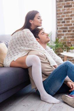 Brunette woman in knee sock hugging boyfriend near couch in living room stock vector