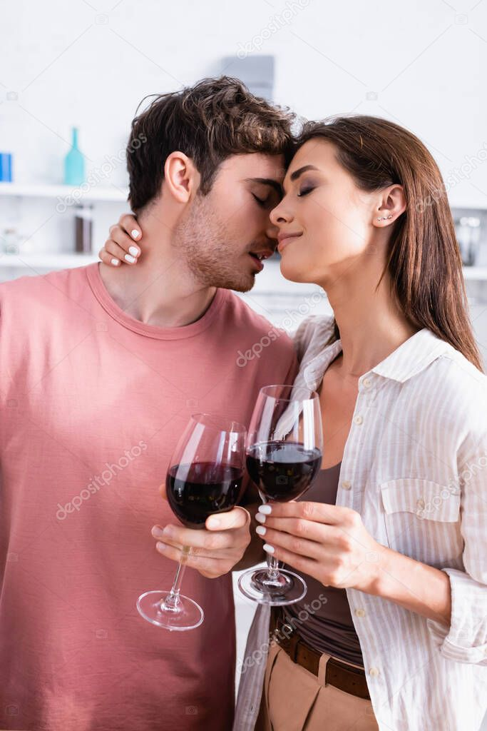 Young woman holding glass of wine and hugging boyfriend with closed eyes in kitchen stock vector