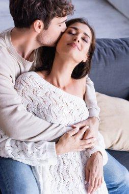 Man kissing brunette girlfriend in knitted sweater in living room stock vector